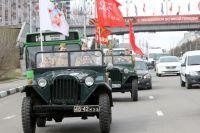 Под красными знаменами по улицам Красноярска едут автомобили времен Великой Отечественной войны.