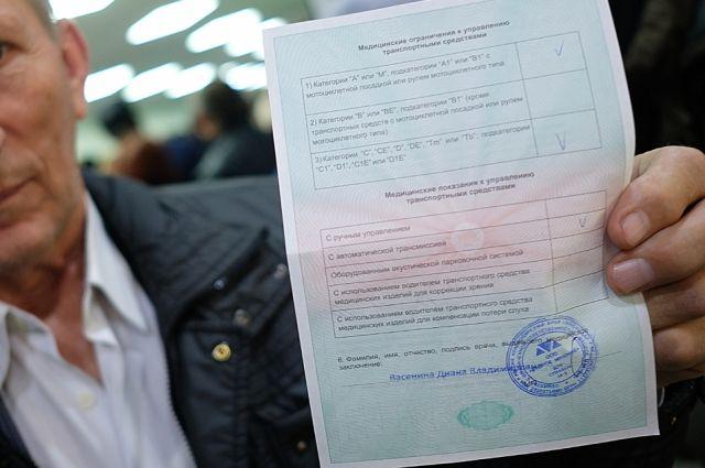 Мужчина демонстрирует медицинское заключение после прохождения транспортной комиссии в медицинском центре в Краснодаре.