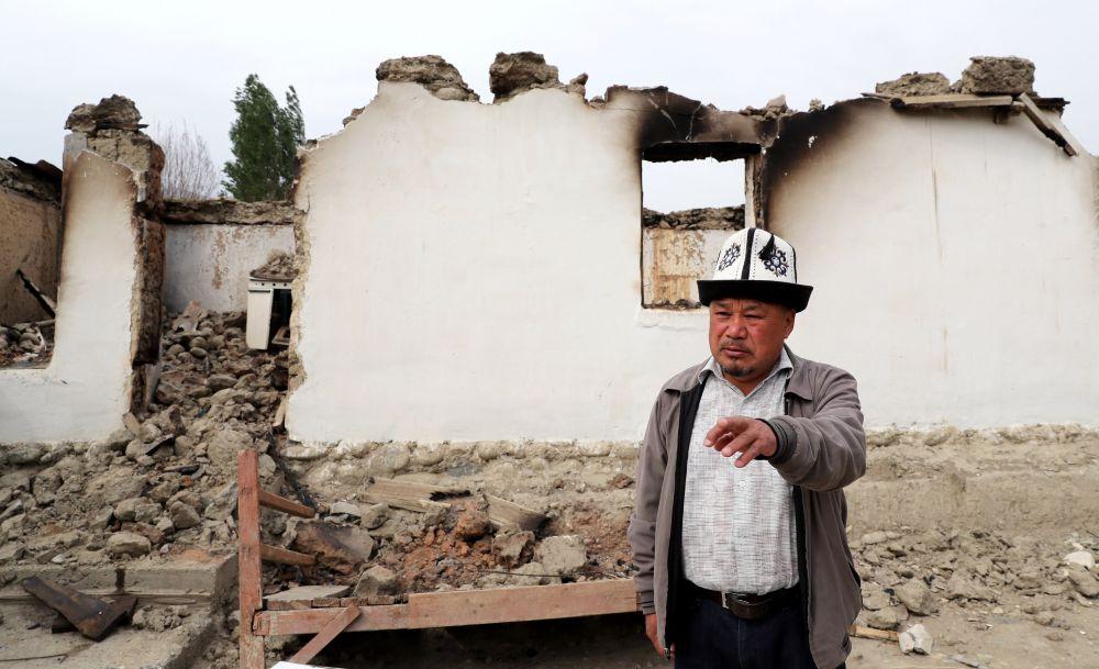 Мужчина стоит у сгоревшего строения в приграничном с Таджикистаном селе Кок-Таш