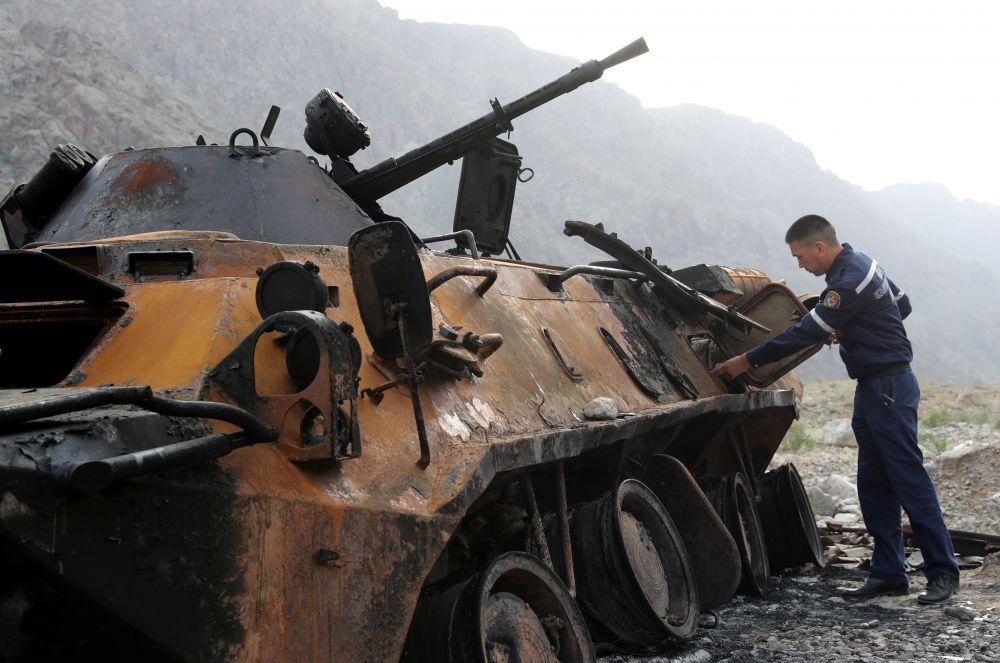 Военнослужащий осматривает сгоревший БТР-80 в районе села Кок-Таш