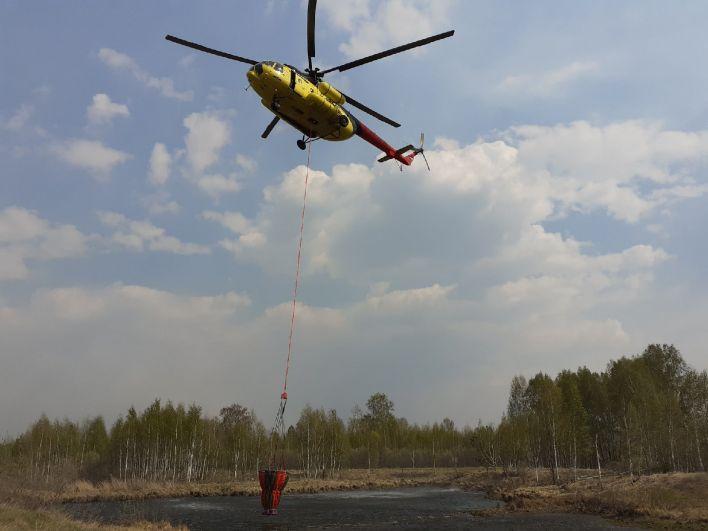 Вертолет забирает воду из водоема. Горят леса: как тушат пожары в Тюменской области, 2021.