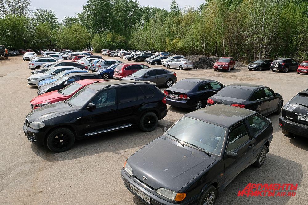 На парковке возле пляжа в Перми много автомобилей.