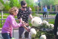 Цветы и игрушки к стихийному мемориалу несут до сих пор.