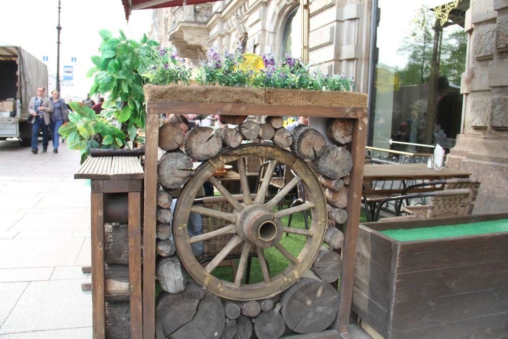 Террасы словно соревнуются в дизайне. Вот такое колесо мы встретили на Невском. Настоящий трактир!