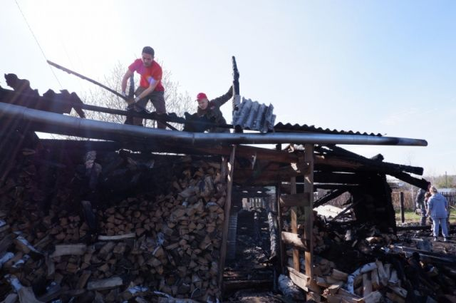 Прибывшая в поселок команда активистов разбирает завалы на пепелище.