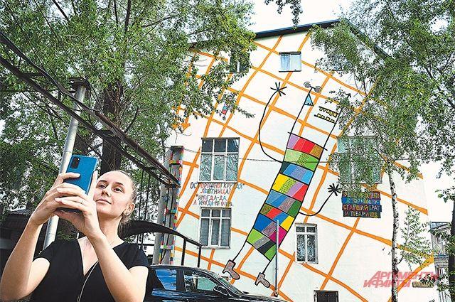 Девушка делает селфи на фоне работы художника Кирилла Кто, выполненной в стиле стрит-арт.