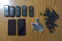Опергруппа нашла четыре полиэтиленовых свертка, в которых находились семь сотовых телефонов и гарнитура.