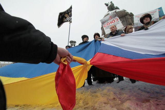 Участники акция «Переяславская Рада вчера — это Таможенный союз сегодня!» у памятника Богдану Хмельницкому в Киеве соединяют флаги Украины и России.