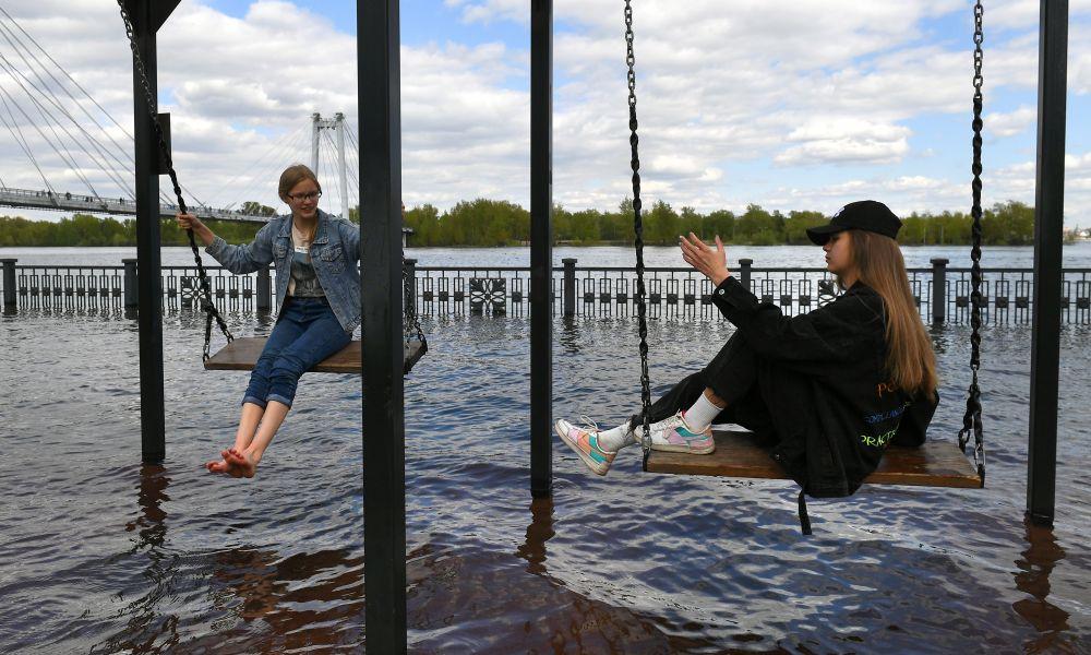 Девушки качаются на качелях на затопленной набережной Енисея в центре Красноярска