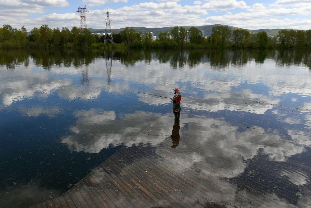 Рыбак на затопленном деревянном тротуаре набережной Енисея в центре Красноярска