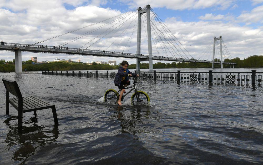 Ребёнок катается на велосипеде по затопленной набережной Енисея возле Виноградовского пешеходного моста в центре Красноярска