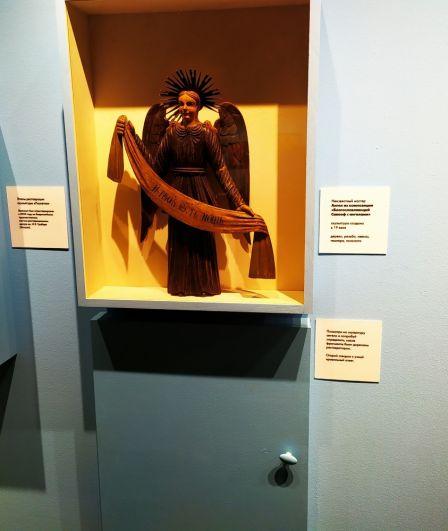 Скульптура ангела (19-й век). Посетителям выставки предлагают угадать, какие фрагменты дорезал реставратор. Узнать ответ можно, открыв дверцу под скульптурой.
