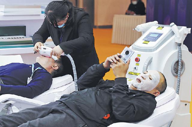 Двое мужчин проходят процедуры по уходу за лицом на Китайской международной выставке индустрии красоты в Пекине, 31 марта.