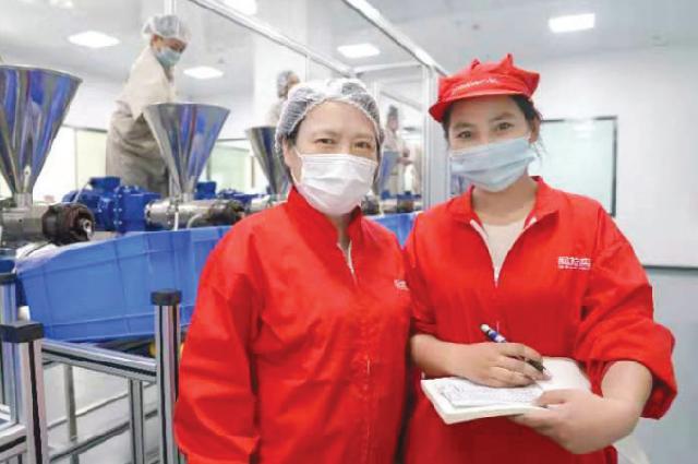 Жэнь Чанъянь (слева) с одной из работниц на заводе в Синьцзян-Уйгурском автономном районе.