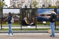 Прохожие на фотовыставке Александра Львова «Русские сезоны. Соловки» на Тверском бульваре в Москве.