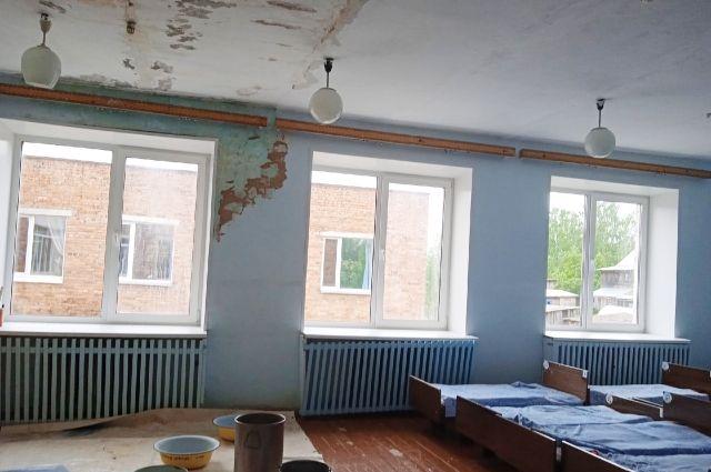 На стене и потолке штукатурка от сырости размокла и осыпается, а пол в детской спальне застелен клеёнкой и заставлен тарой для сбора воды.
