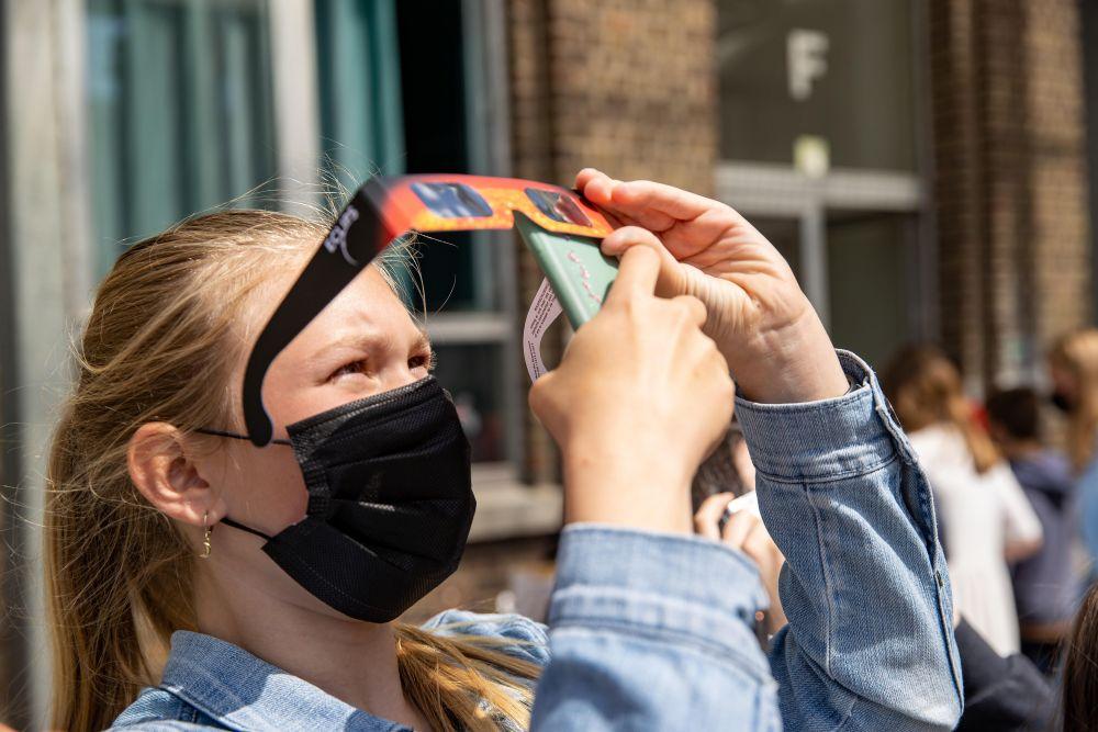Люди наблюдают солнечное затмение в городе Руселаре (Бельгия)