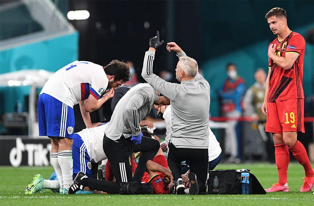 Медики оказывают помощь игроку сборной Бельгии Тимоти Кастаню после его столкновения с игроком сборной России Далером Кузяевым.