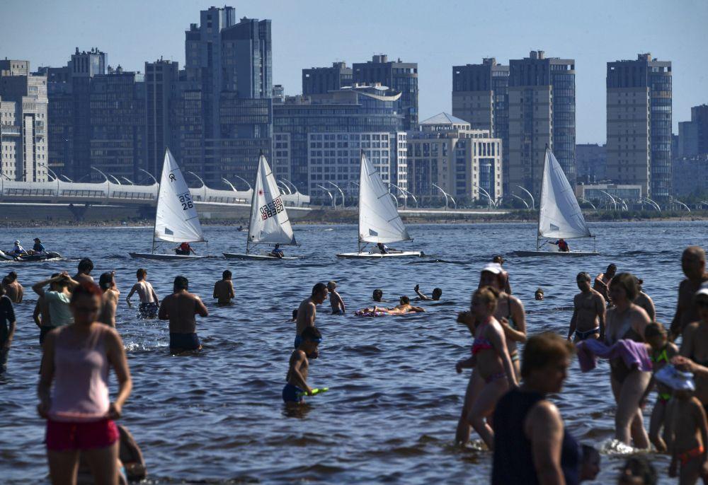 Люди купаются в акватории Финского залива рядом с парком 300-летия Санкт-Петербурга