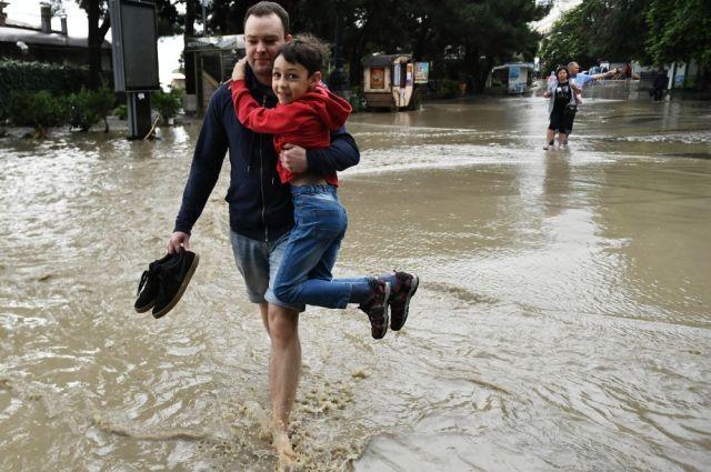 Мужчина с ребенком на одной из улиц Ялты после затопления проливными дождями, Крым, Россия, 18.06.2021 г.