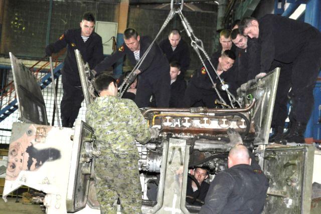 Морпехи извлекают из корпуса силовую установку БМП-3.