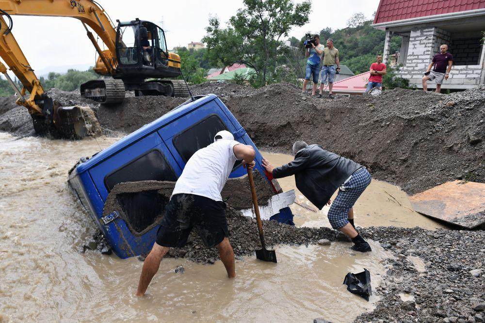 Спецтехники и местные жители на улице Джафера Сейдамета в Ялте во время ликвидации последствий наводнения