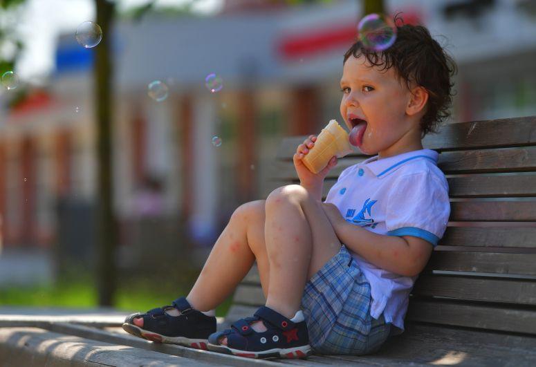 Мальчик ест мороженое в жаркую погоду