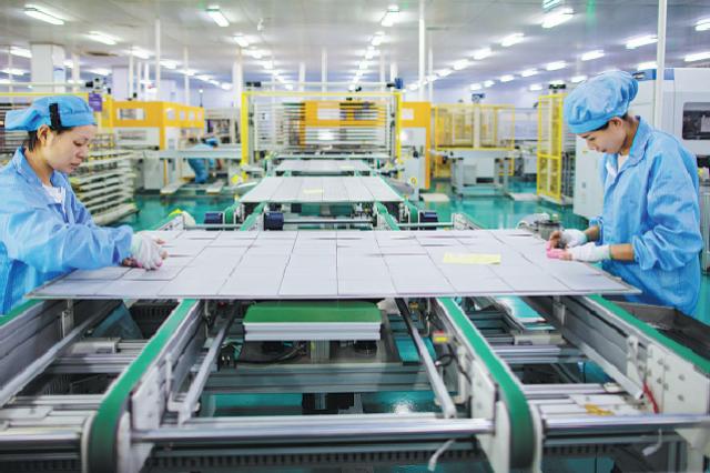 Сотрудники новой энергетической компании производят высокоэффективные солнечные панели в Хайане, провинции Цзянсу.