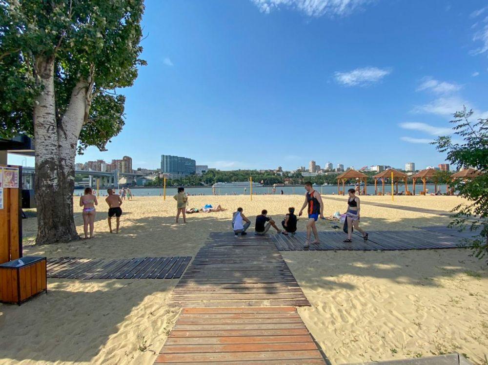 Люди купаются, загорают, устраивают пикники на пляже.