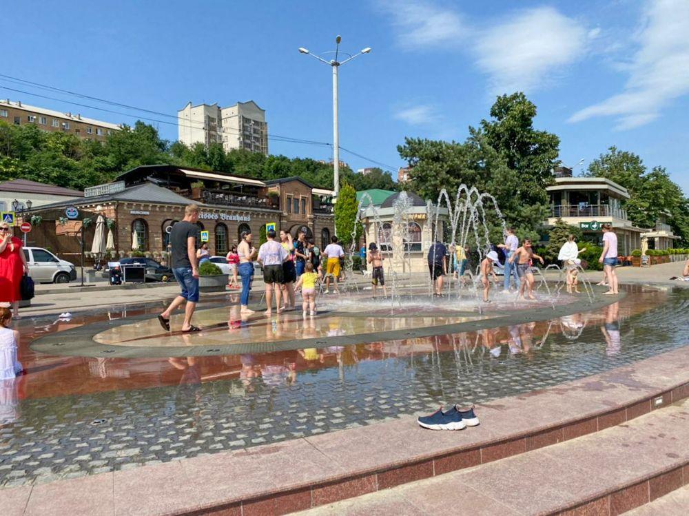Взрослые и дети спасаются от жары в фонтане. Главное, не забыть кроссовки.