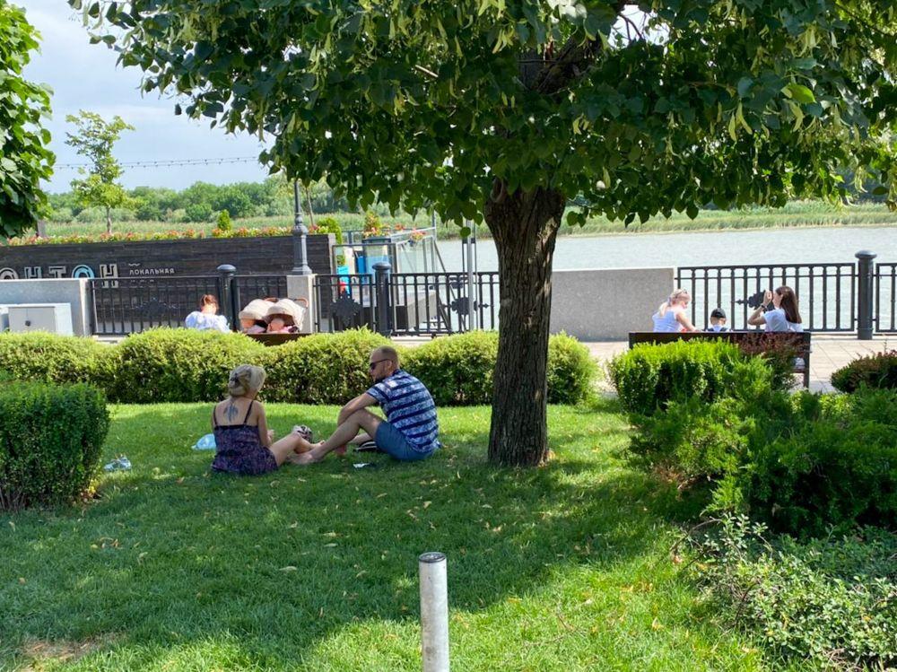 Влюблённая парочка устроила себе небольшой пикник в парке на Набережной.