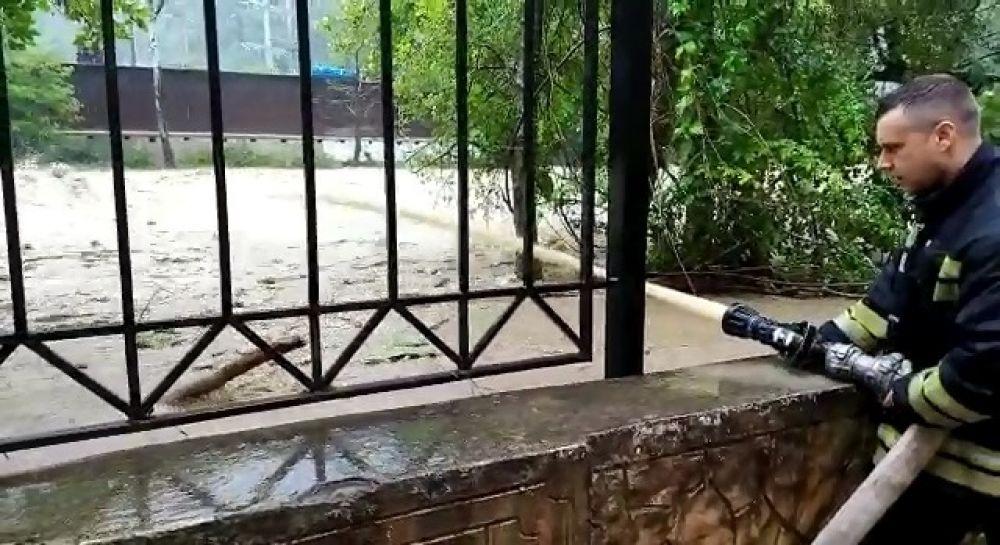 Сотрудники экстренных служб отводят воду с улиц города.