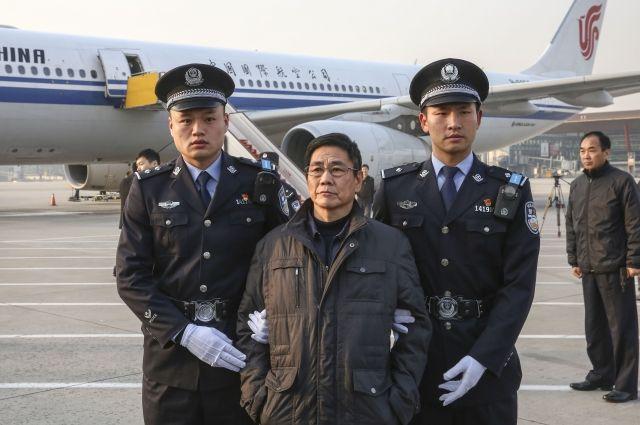 Полиция сопровождает Яо Цзиньци в Пекине. Яо Цзиньци — подозреваемый в совершении преступления бывший заместитель главы округа Синьчан на востоке Китая. Его экстрадировали из Болгарии. Яо, бежавший за границу в декабре 2005 года, стал первым бывшим государственным служащим, которого Китай экстрадировал из страны-члена ЕС. 2018 г.