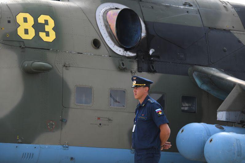 Военнослужащий у российского транспортно-боевого вертолёта Ми-35М на Международном авиационно-космическом салоне МАКС-2021