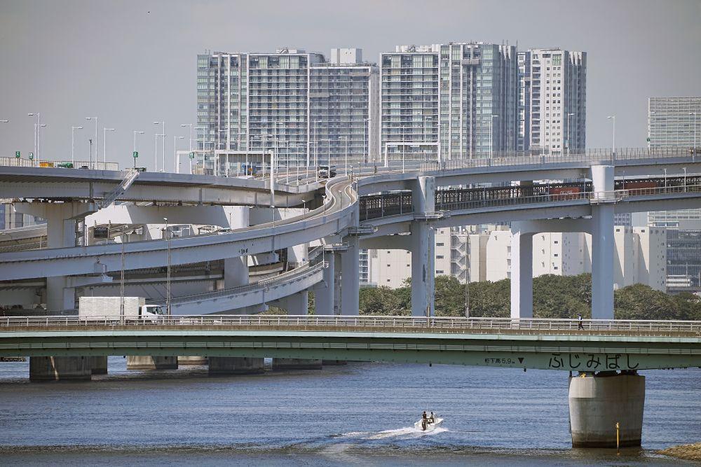 Моторная лодка проходит под многоэтажным автомобильным мостом