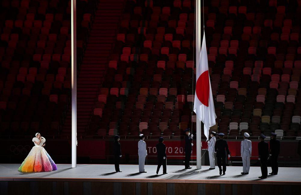 Певица MISIA (слева) выступает во время поднятия флага Японии на церемонии открытия на Национальном олимпийском стадионе