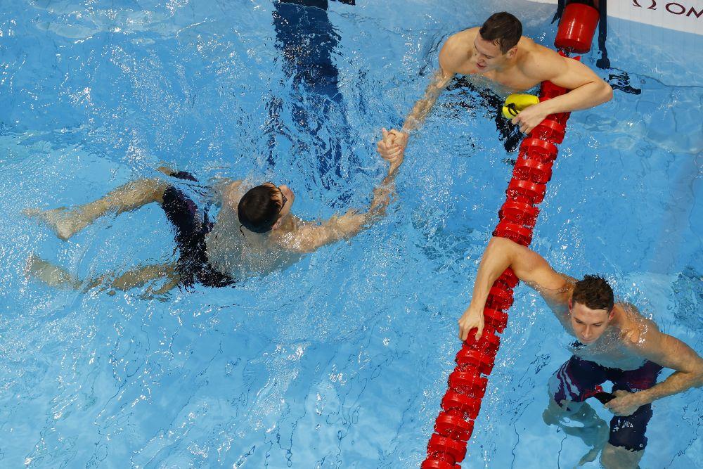 Российский спортсмен Евгений Рылов и австралийский спортсмен Митч Ларкин после финального заплыва на 100 метров на спине среди мужчин на XXXII летних Олимпийских играх