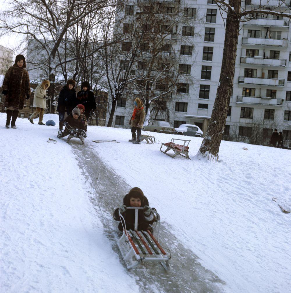 Детские санки. Дети катаются на санках с ледяной горки