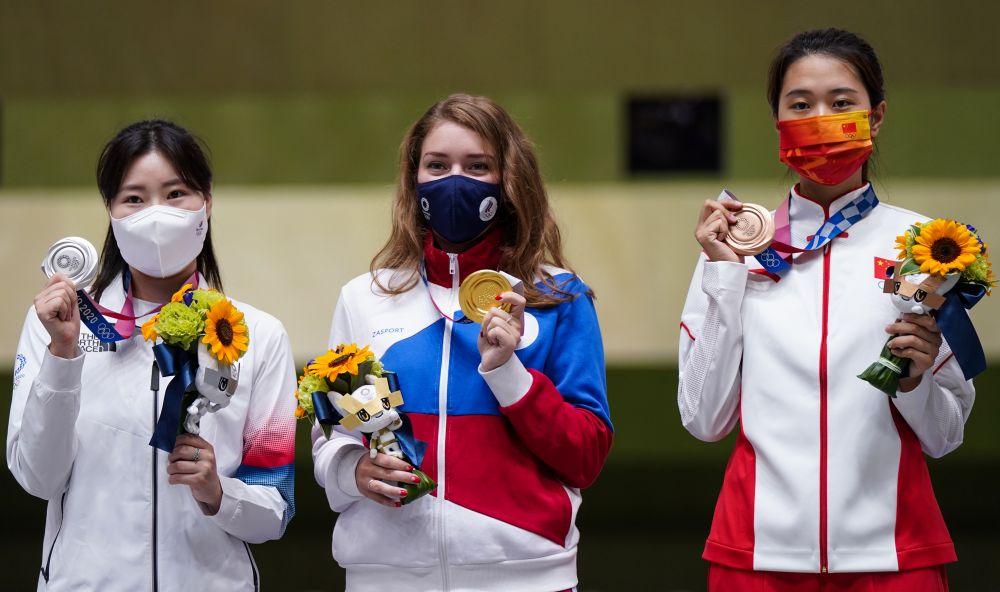Призеры соревнований по стрельбе из пневматического пистолета с 25 метров среди женщин на XXXII летних Олимпийских играх в Токио на церемонии награждения (слева направо): Ким Минджон (Республика Корея) - серебряная медаль, российская спортсменка, член сборной России (команда ОКР) Виталина Бацарашкина - золотая медаль, Сяо Цзяжуисюань (КНР) - бронзовая медаль