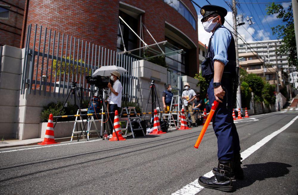 Полицейские и журналисты у посольства Польши в Токио, куда прибыла белорусская спортсменка Кристина Тимановская