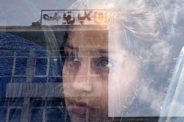 Лицо девочки в отражении от витрины одного из магазинов в Кабуле, Афганистан.