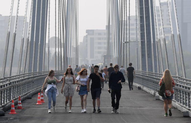 Прохожие на Виноградовском пешеходном мосту, соединяющем левобережную набережную с островом Татышев на Енисее, в Красноярске