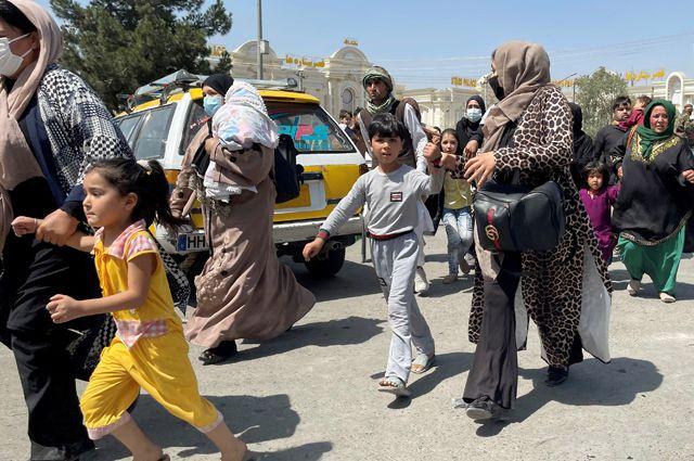 Женщины с детьми пытаются попасть внутрь международного аэропорта им. Хамида Карзая в Кабуле.