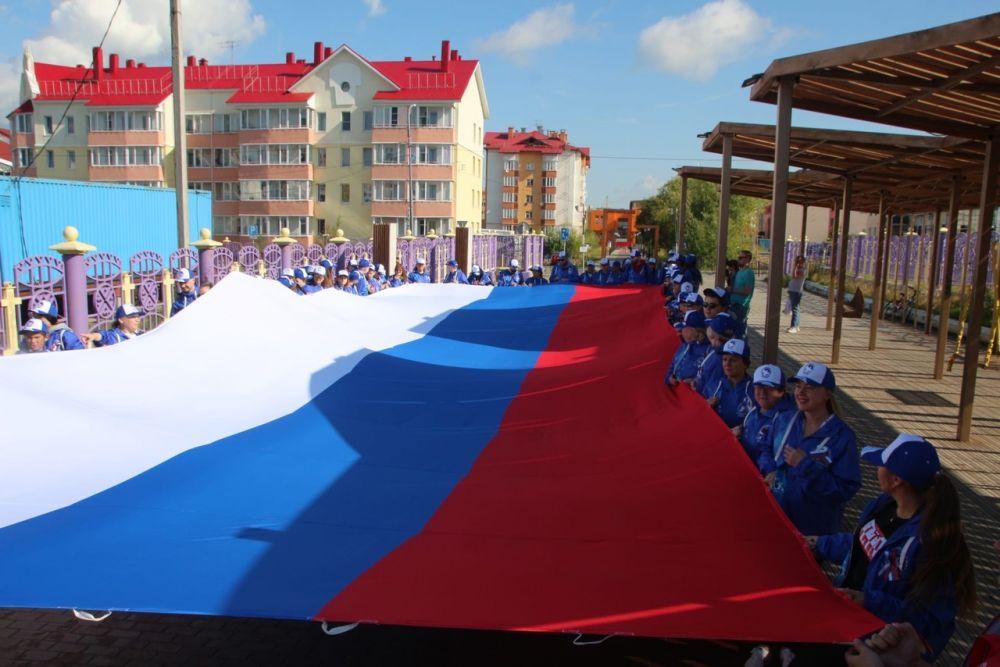 В Салехарде пронесли 15-метровое полотно российского триколора от качельного парка у первой школы до городского сада.