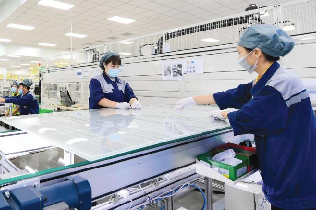 Рабочие собирают заготовки солнечных элементов на заводе в городе Иу, провинция Чжэцзян, июнь.