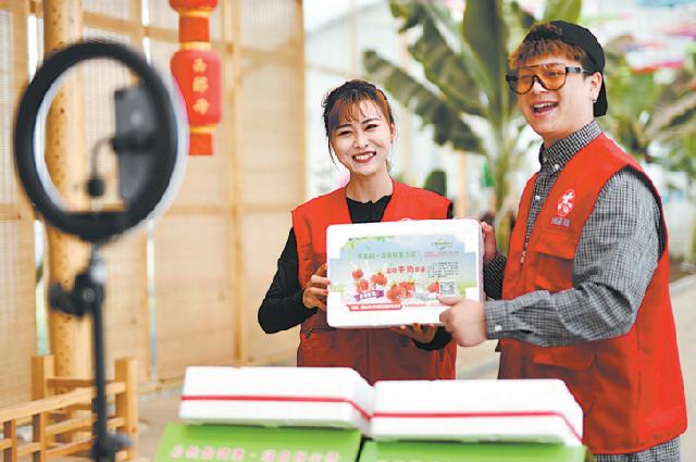Работники рекламируют фрукты через прямую трансляцию в деревне в районе Фэнжунь города Таншань, провинция Хэбэй, 11 мая 2021 года.