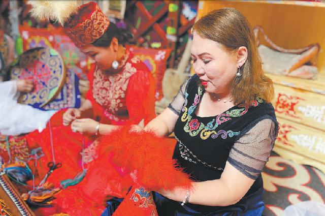 Дженисгуль Нуртанакин сортирует вышитые изделия, которые она создала вмастерской в г. Инин, Синьцзян-Уйгурский автономный район