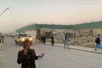 Люди покидают место взрыва в аэропорте Кабула.