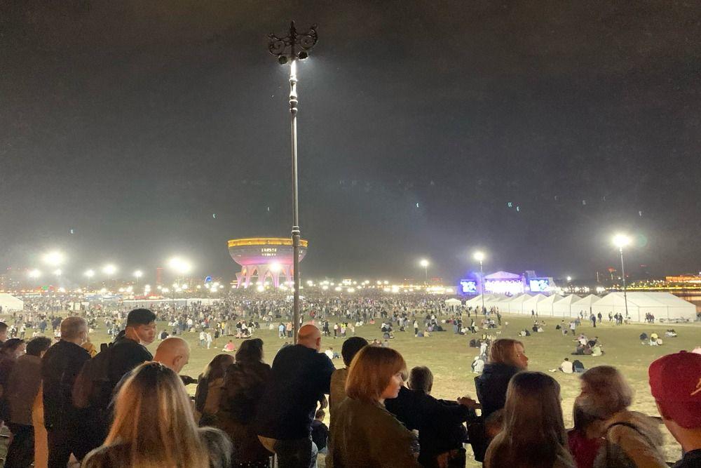 Зрители смотрят концерт за оградой.