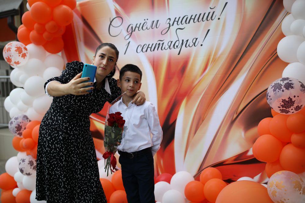 Женщина фотографируется со своим ребёнком во время праздничных мероприятий, посвящённых Дню знаний, в школе №94 в Краснодаре. В этой школе набрали первые классы на все буквы алфавита. Всего в учебное заведение было принято 840 учеников первого класса